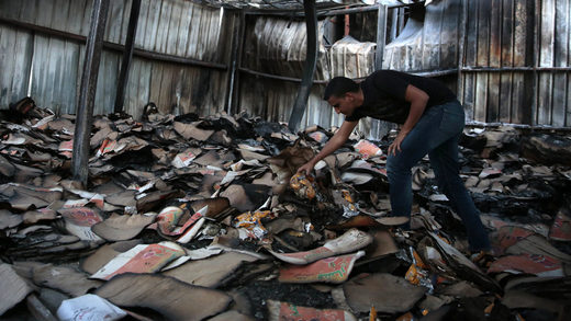 man inspects a food factory hit by Saudi-airstrikes, in Sanaa
