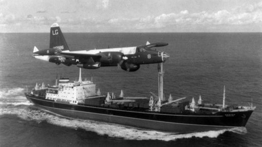 A US Navy P-2H Neptune of VP-18 flying over a Soviet cargo ship with crated Il-28s on deck during the Cuban Crisis